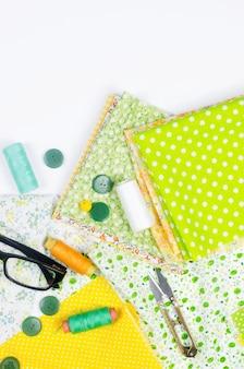 Tissus colorés jaunes et verts, ciseaux, boutons, bobines de fil et verres sur blanc.