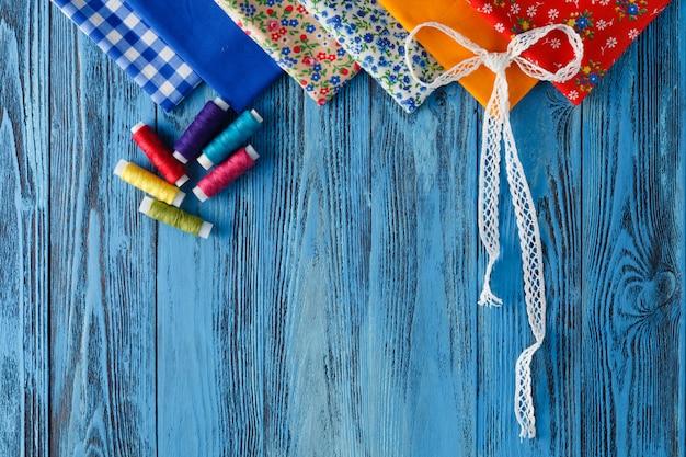Tissus en coton à coudre, dentelles et accessoires pour travaux d'aiguille sur fond de bois.
