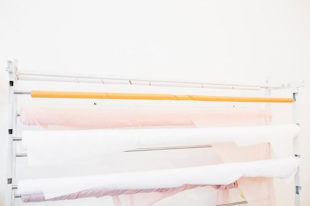 Des tissus roses et blancs enroulés dans un magasin de tailleur
