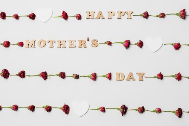 Titre de fête des mères heureux entre fleurs aromatiques fraîches et coeurs d'ornement