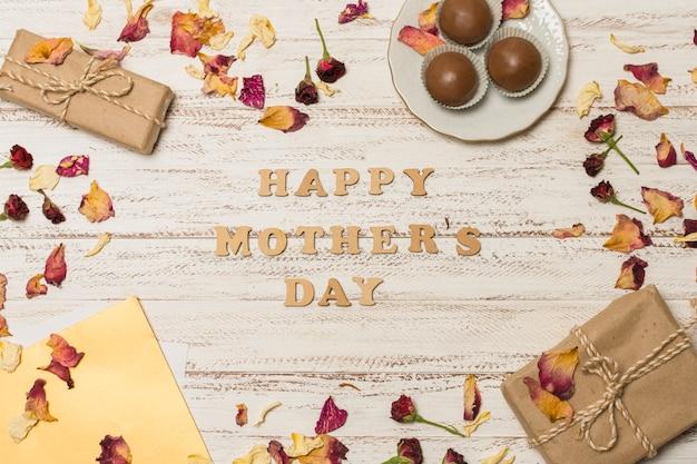 Titre de fête des mères heureux entre papier près de la plaque avec des bonbons et des boîtes à cadeaux