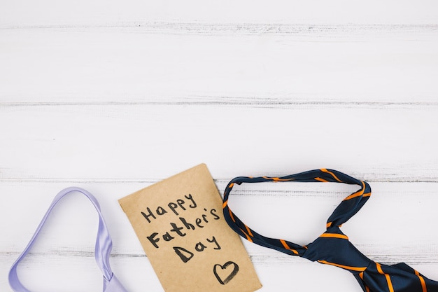 Titre de fête des pères heureux sur du papier kraft près des cravates