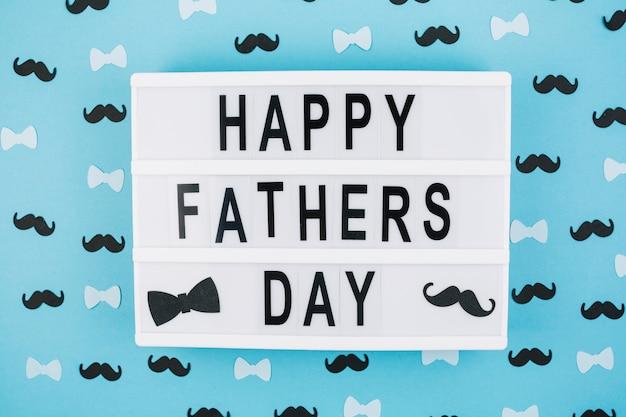 Titre de fête des pères heureux sur tablette entre les décorations