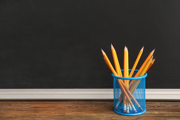 Titulaire avec des crayons sur la table en classe