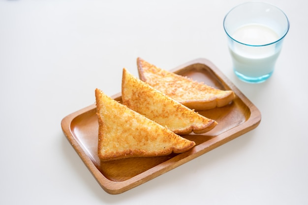 Toast au fromage croustillant sur une plaque en bois sur fond blanc avec du lait en verre