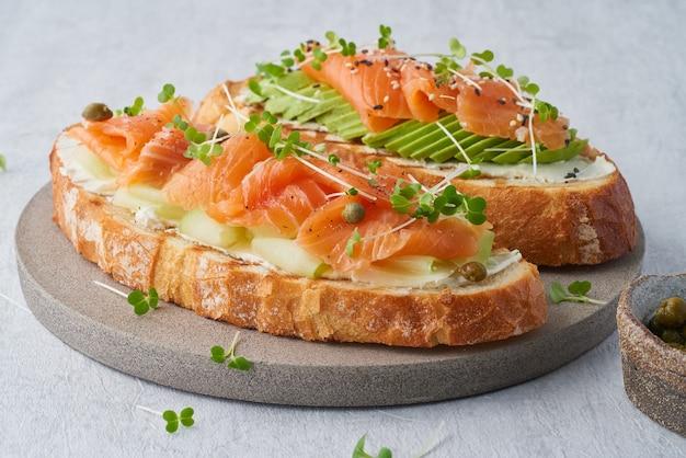 Toast au saumon, fromage à la crème et tranches de concombre sur table en béton blanc