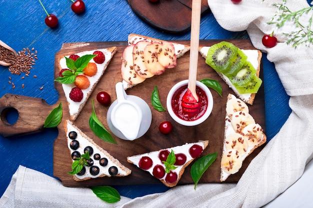 Toast aux fruits sur une planche en bois sur une surface bleue et rustique,