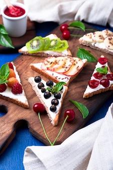 Toast aux fruits sur une planche en bois sur une surface rustique bleue