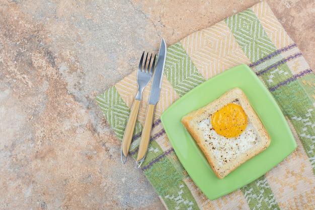 Toast aux oeufs aux épices sur plaque verte avec couverts et nappe