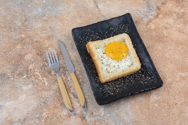 Toast aux œufs avec des épices sur plaque noire avec des couverts