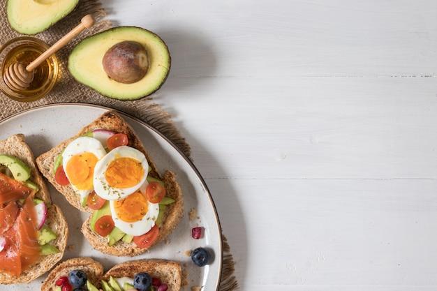 Toast à l'avocat avec garniture différente, y compris poisson de saumon, œufs, baies