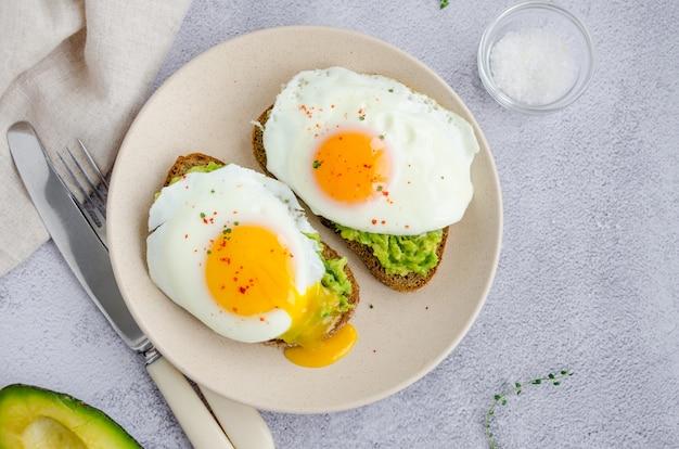 Toast à l'avocat avec œuf au plat et sel de mer sur une plaque sur fond gris. petit déjeuner ou déjeuner sain. orientation horizontale