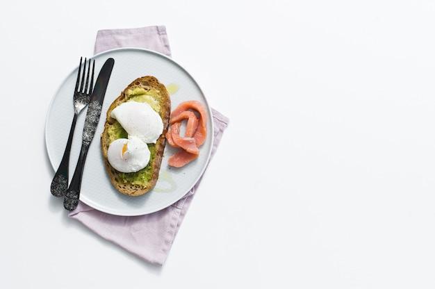 Toast avec avocat, oeuf, saumon et pain noir.