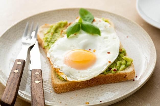 Toast à l'avocat avec œufs au plat et petits pois frais, tasses à café. petit-déjeuner sain, nourriture céto. concept de régime.