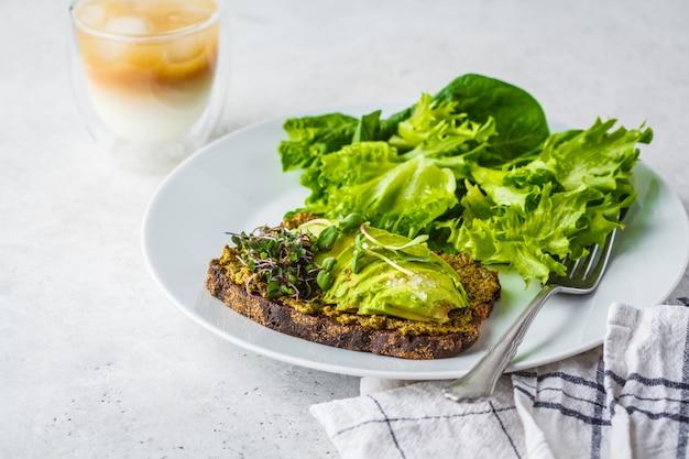 Toast à l'avocat avec pesto, pousses et salade sur une plaque blanche.