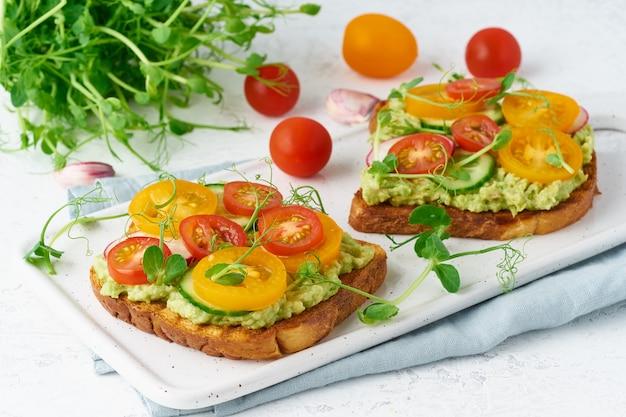 Toast à l'avocat avec tomates cerises et herbes, petit déjeuner, gros plan