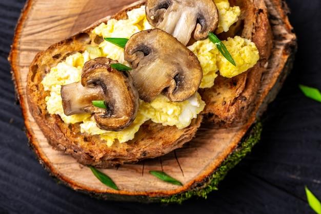 Toast de blé entier avec œufs brouillés aux champignons et fromage cottage. petit-déjeuner ou brunch santé.