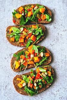 Toast avec citrouille et roquette. sandwichs ouverts à la citrouille. toasts végétaliens sains avec des légumes verts et de la citrouille. collation automnale. bruschetta à la roquette et à la citrouille.