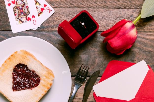 Toast avec de la confiture sur une assiette près de cartes à jouer, fleur, enveloppe et bague dans une boîte cadeau
