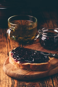 Toast avec de la confiture de baies sur une planche à découper et une tasse de thé vert