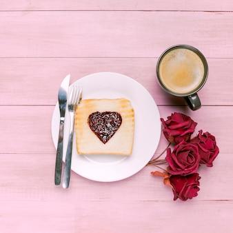 Toast avec de la confiture en forme de coeur avec des roses et du café
