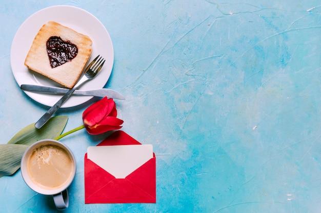 Toast avec de la confiture en forme de coeur avec des tulipes sur la table