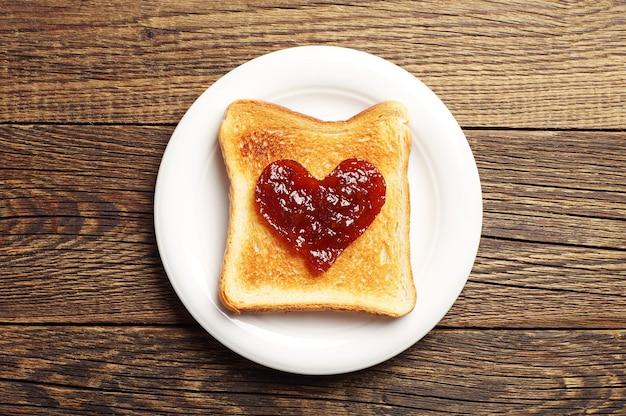 Toast avec confiture en forme de coeurs sur fond de bois. vue de dessus