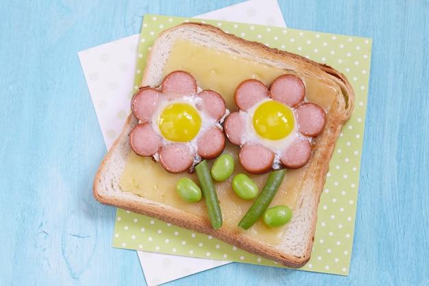 Toast drôle avec du fromage et des fleurs faites de saucisses, haricots verts et œufs de caille