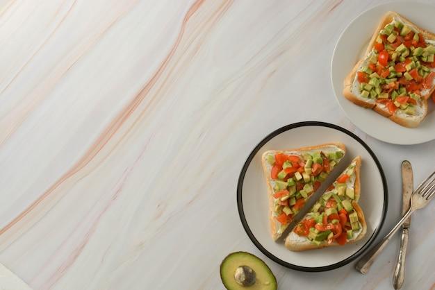 Toast avec du fromage à la crème, avocat et tomates cerises. la nourriture saine. espace de copie.
