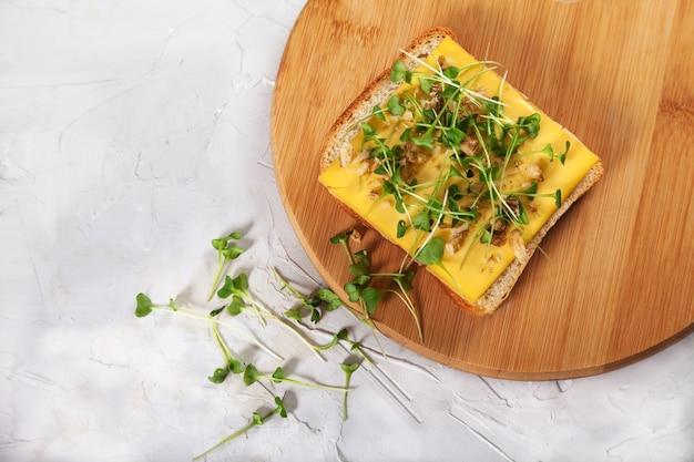 Toast avec du fromage et des pousses de brocoli sur une planche de bois.