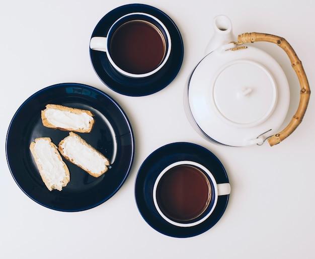 Toast avec du fromage; tasse à café et théière sur fond blanc