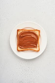 Toast frais avec de la pâte de chocolat sur une plaque blanche sur fond gris