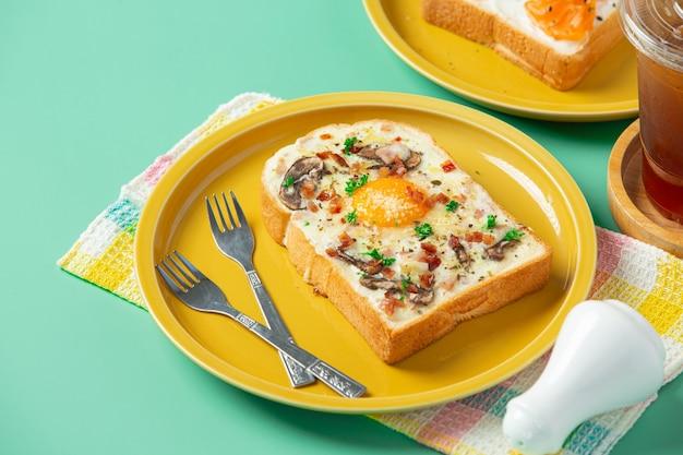 Toast avec oeuf au plat et fromage à la crème sur fond vert pastel