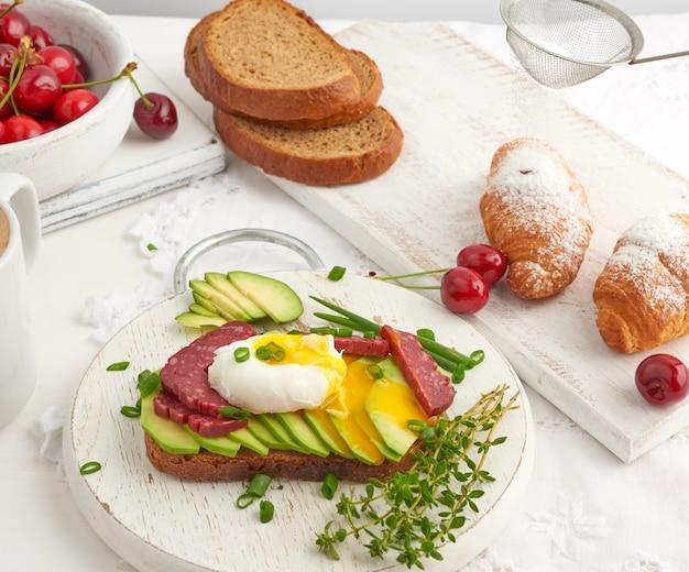 Toast avec œuf poché et avocat sur une planche ronde