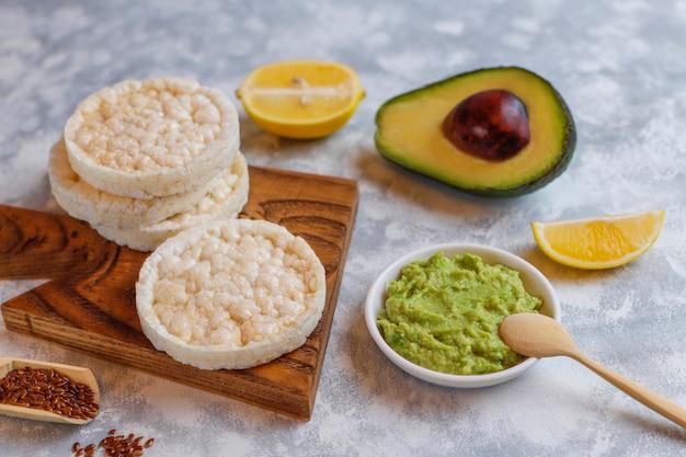Toast ouvert aux avocats avec pain de riz, tranche de citron, tranches d'avocat, vue de dessus des graines.