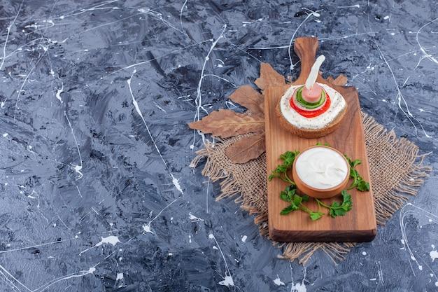 Toast pain avec de la crème sure et des légumes tranchés sur une planche à découper en bois.
