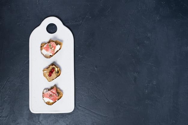 Toast avec parme, salami et pâté d'oie sur une planche à découper blanche