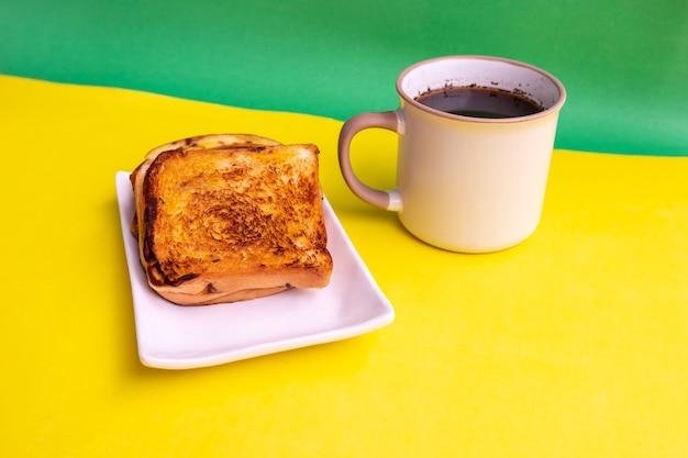 Toast sur plaque blanche et tasse de café noir sur fond de papier jaune et vert. toast et café noir pour le petit déjeuner. photo horizontale