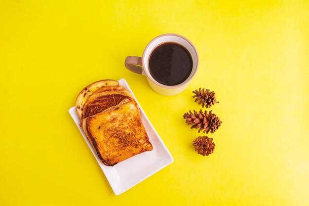 Toast sur plaque blanche et tasse à café noire avec décoration de fleurs d'épinette sur fond de papier jaune. toast et café noir pour le petit déjeuner. photo horizontale