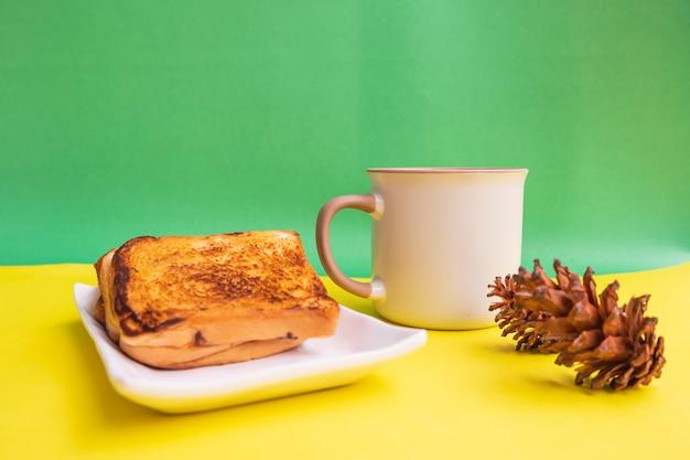 Toast sur plaque blanche et tasse à café noire avec décoration de fleurs d'épinette sur fond de papier jaune et vert. toast et café noir pour le petit déjeuner. photo horizontale