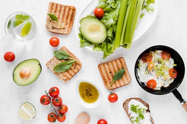 Toast plate poser avec des tomates avocat et des œufs