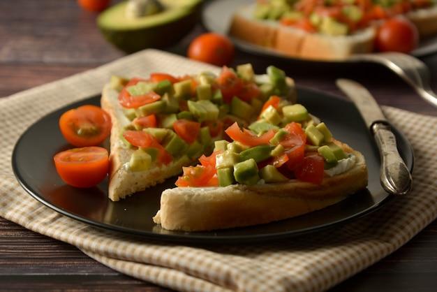 Toast sain avec avocat, tomates cerises et fromage sur une assiette. table en bois.