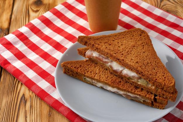 Toast sandwich dans une assiette et une tasse de café sur une serviette sur une table en bois