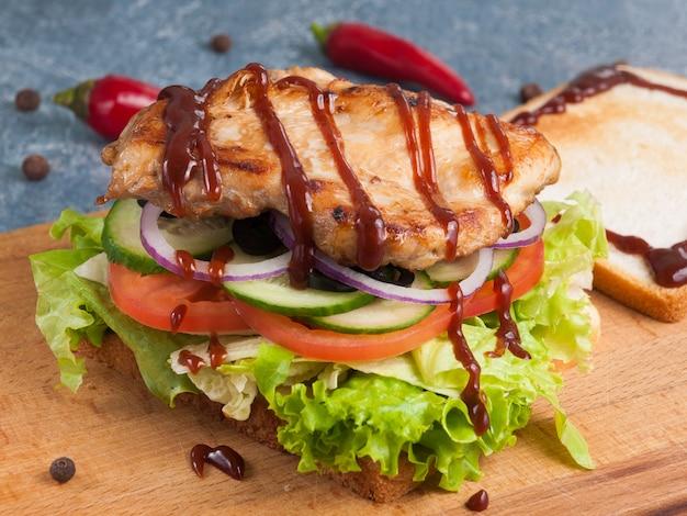 Toast ou sandwich avec filet de poulet grillé sauce barbecue et légumes