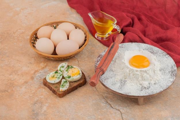 Toast savoureux avec plusieurs œufs et huile sur table en marbre.