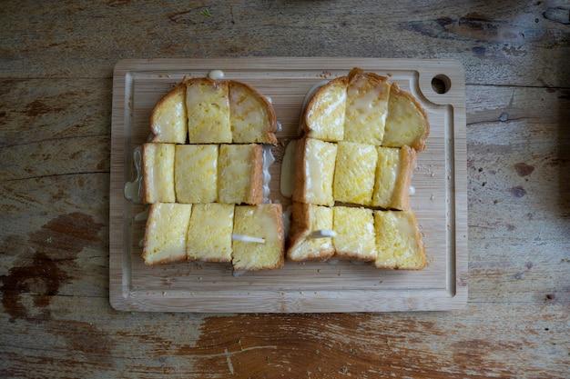 Toast surmonté de lait, placé sur un plateau en bois.