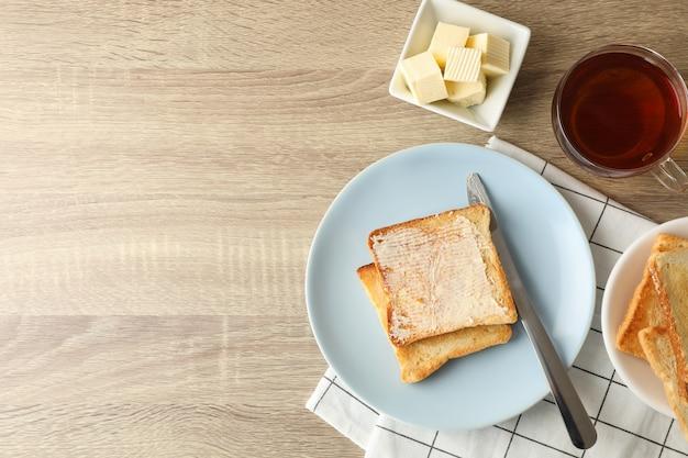 Toasts sur assiette, serviette, thé et beurre sur fond de bois, espace copie