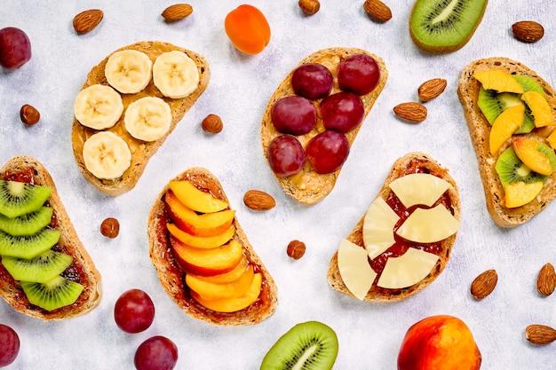 Toasts au beurre d'arachide, confiture de fraises, banane, raisins, pêche, kiwi, ananas, noix