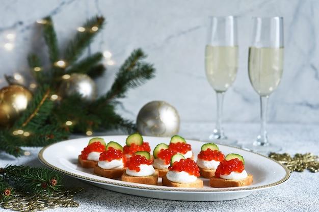 Toasts au fromage et caviar rouge sur une table du nouvel an avec champagne. table du nouvel an. collation.