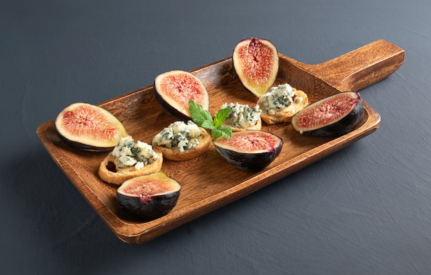 Toasts au fromage roquefort et figues fraîches, sur une planche de service en bois